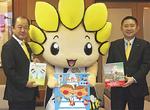 寄贈した絵本を手にする、座間事業所の小野裕幸課長(右)と遠藤市長、ざまりん