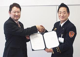 協定書を締結し、握手を交わす篠崎消防長(右)と渡病院長