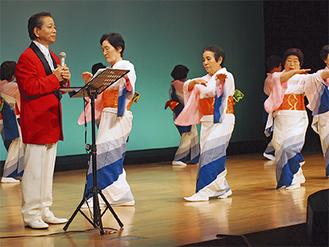 嶋さん(左)の歌に合わせて踊る会員