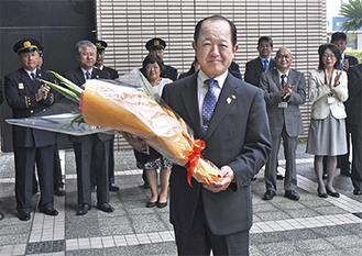 市役所玄関で職員から、花束を受け取った遠藤市長。初登庁には多くの職員が駆け付けた