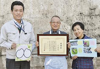 感謝状と子どもたちからのメッセージカードを手に喜ぶ村上さん(中央)と妻・尚子さん。左は矢部園長