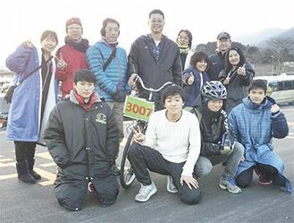 21位を喜ぶ選手たち。前列左から小宮さん、溝渕さん、小松さん、松本さん。後列中央でハンドルを握るのが前里さん