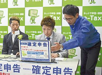 税務署職員に教えてもらいながら確定申告を体験する尚弥さん(中央)