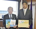 絵本と紙芝居を手にする遠藤市長と磯さん