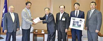 草薙代表(左から2人目)に目録を手渡す菅会長(同3人目)と両者を紹介した関係者など