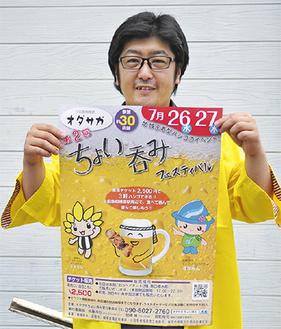 ポスターを手にする佐藤実行委員長