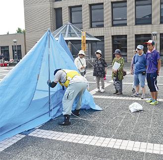 ブルーシートを用いたテント張りを学ぶ参加者