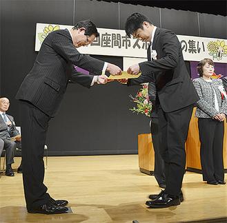沖本会長(左)から表彰状を受け取る受賞者