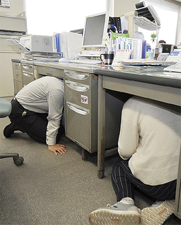 机の下で頭を守る市職員