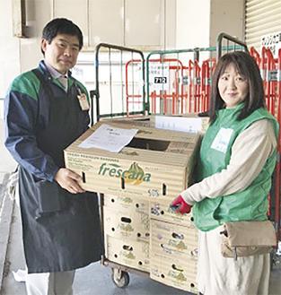 食品の寄贈を受ける松本理事長(右)