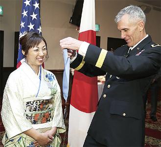 ジェームズ・パスカレット司令官(右)からメダルを授与される田村香織さん=在日米陸軍基地管理本部提供