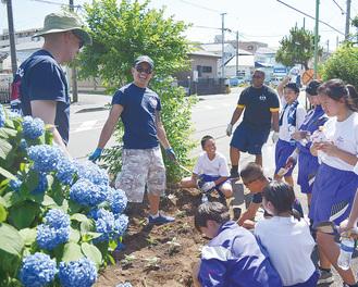 談笑しながらひまわりを植える南中の生徒と厚木基地の兵士