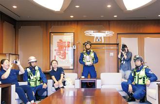 座間市庁舎市長応接室で寄贈された小型無人飛行機ドローンを操縦する座間市消防署員(中央)=6月29日