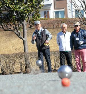 金属の球を投げて相手より的に近づける。カーリングのように頭脳と技術を楽しむ=かにが沢公園/2月4日撮影