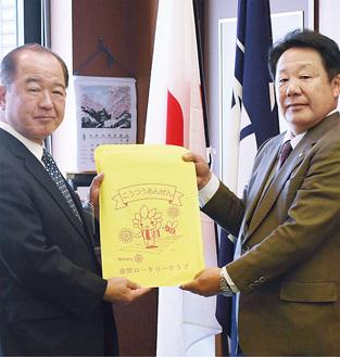 ランドセルカバーを遠藤市長に手渡す今井均会長(右)。