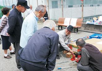 防災倉庫にある機材の説明を受ける住民たち