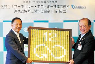 「持続可能な消費と生産のパタンを確保する」という目標デザインを手にする遠藤三紀夫座間市長(右)と(株)小田急電鉄の星野晃司取締役社長。