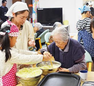 お好み焼きを一緒に作る子どもと施設の利用者と地域のボランティア=10月28日、愛の家グループホーム座間西栗原