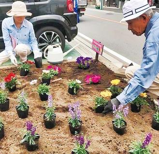 苗を植える小山克幸さんと美和さん夫婦(提供写真)