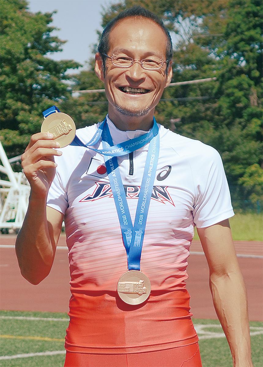 金メダル、銅メダルを手に笑顔の宮本義久さん