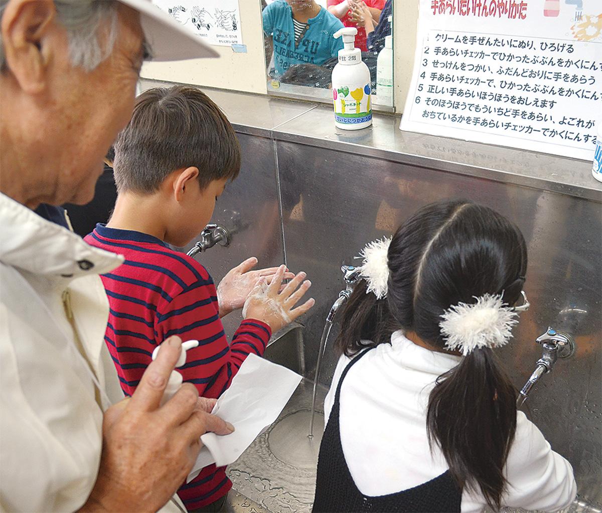 手洗いマイスター指導のもと手を洗う児童