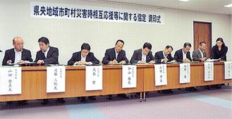 協定書に調印する小林市長(左から5人目)