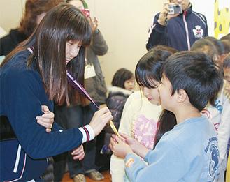 秋山さん(左)が獲得した金メダルを触る児童