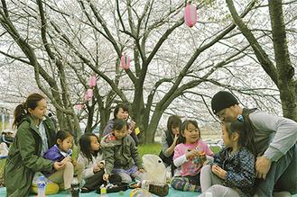 桜の下で食事を楽しむ花見客(3月23日撮影)