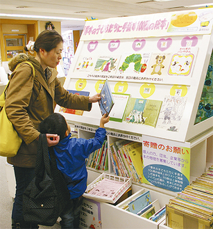 図書館に展示されている絵本を選ぶ親子
