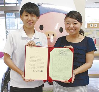 プレゼントしている記念証書(見本)を持つ市民課の職員