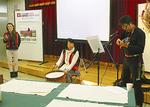民族楽器で弾き語りをする松橋さん(右)
