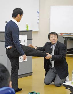 参加者に実演させる廣戸さん(右)