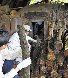 炭の材料となる原木を窯に入れていく参加者