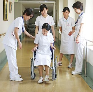 看護師に指導を受け、車いすを体験する高校生