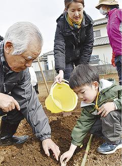 開校式でジャガイモの植え付けをする参加者ら