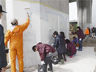 一心にペンキを塗る地域住民たち