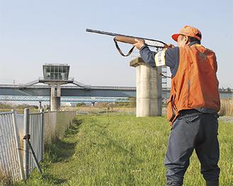 相模川でカワウに向けて銃を構える猟友会会員