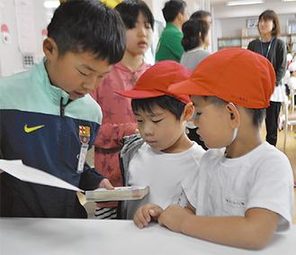 図書館で貸し出しを手伝う図書委員の6年生(左)と1年生ら