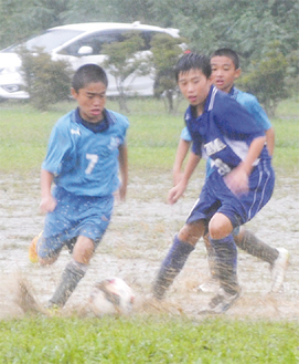 泥まみれでドリブルするDREAMSの選手(左)