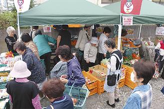 地場野菜や日用品を買い求める地域住民