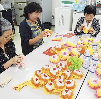 慣れた手つきで花を作る会員たち