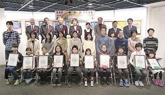 入賞した子どもたちと関係者で記念撮影(チームアトム提供)アトム大賞を受賞した有江さんの作品名は「がんとりくん」