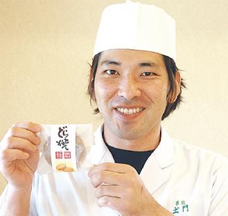 ユニクロのロゴが入ったどら焼きを手にする土門社長
