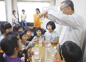 座学のあとの科学実験のようす。講師は日本イオン(株)の代表取締役・中島有二さん。イオン成分の効能などが一目でわかる実験に子どもたちは楽しみながら学んだ