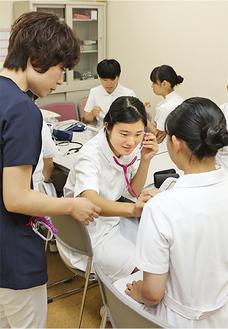現役看護師から聴診器の使い方を習う高校生たち