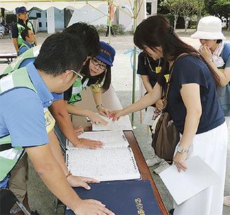 ボランティア役(右)に地図を使って派遣先までの行き方を説明する社協職員と厚木JCメンバー