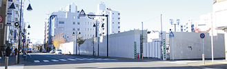 建物が取り壊され、白い囲いに覆われている現地=12月6日撮影
