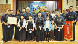 受賞を喜ぶ剣士会の会員たち。後列左から5人目が初代会長の長崎尚さん。右端が鄭会長、前列右端が長崎和代さん