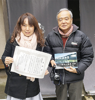 優秀賞を受賞し、作品の書籍化が決まった加藤久美子さん(左)と、応募のきっかけとなった本を持つ著者の森義晴さん=2月2日、市内七沢の福元館前で撮影