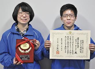 賞状を手にする代表の近藤さん(左)と盾を持つ副代表の横山結さん(情報学部1年)。「KAIT BLUE」のイメージカラーであるブルーのジャンパーには「社会の治安を守る」意味が込められている